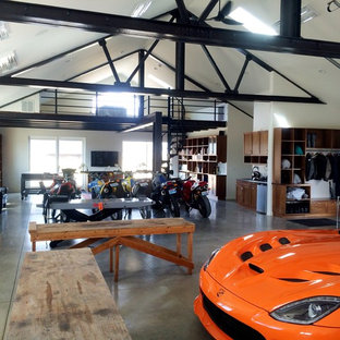 Inspiration for a large industrial attached four-car garage workshop remodel in Other