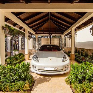 На фото: отдельно стоящий гараж в средиземноморском стиле с навесом для автомобилей с