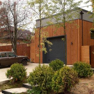 На фото: отдельно стоящий гараж среднего размера в современном стиле для одной машины с