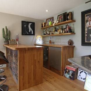 This is an example of a contemporary galley breakfast bar in Surrey with wood worktops, no sink, open cabinets, medium wood cabinets and medium hardwood flooring.
