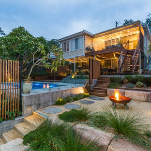 Tropical backyard full sun xeriscape in Newcastle - Maitland with a fire feature and gravel.