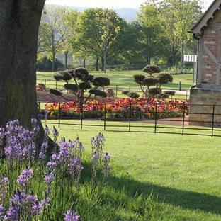 Exemple d'un très grand jardin arrière tendance l'été avec un massif de fleurs et des pavés en pierre naturelle.