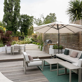 Inspiration for a large contemporary back garden in London with a potted garden and decking.