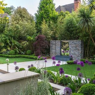 Bild på en stor tropisk trädgård, med en fontän och naturstensplattor