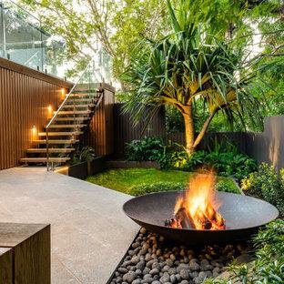 На фото: маленький летний участок и сад на внутреннем дворе в современном стиле с местом для костра, полуденной тенью и покрытием из каменной брусчатки с