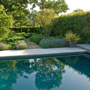 Large victorian backyard partial sun formal garden in Sussex with natural stone pavers for summer.