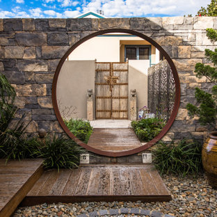 This is an example of an asian partial sun garden in Wollongong with a garden path and decking.