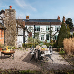 This is an example of a large farmhouse back garden in Other with a fire feature and gravel.