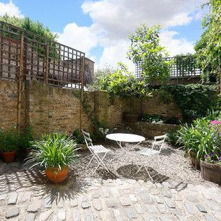 Kleiner, Halbschattiger Moderner Kiesgarten im Sommer, hinter dem Haus mit Gartenmauer in London
