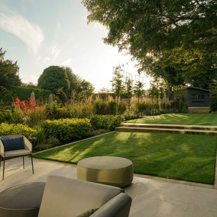 Large contemporary back formal garden in London with concrete paving.