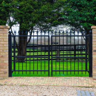 Cette photo montre un jardin nature avec un portail et des pavés en brique.