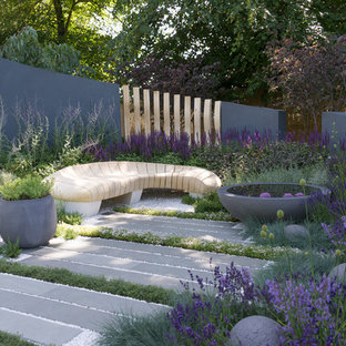 This is an example of a medium sized contemporary back full sun garden in Berkshire with natural stone paving and a pond.