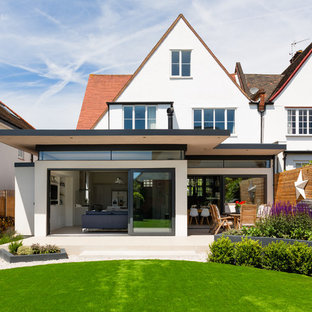 Contemporary back full sun garden in London with a retaining wall.