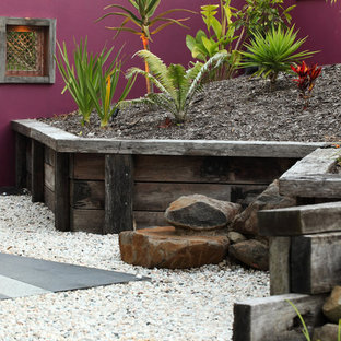 This is an example of a tropical garden in Sunshine Coast with gravel.