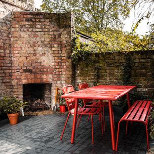 Kleines, Halbschattiges Modernes Garten im Innenhof im Sommer mit Kamin und Pflasterklinker in London