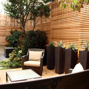 Design ideas for a mid-sized traditional partial sun courtyard landscaping in London with decking.