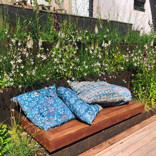 Стильный дизайн: солнечный, летний участок и сад среднего размера на склоне в стиле кантри с подпорной стенкой, освещенностью и покрытием из каменной брусчатки - последний тренд