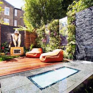 This is an example of a world-inspired back formal garden in London with a water feature and decking.