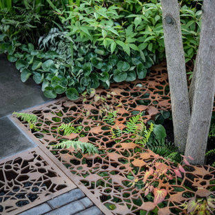 Design ideas for a medium sized modern back formal partial sun garden in London with brick paving.