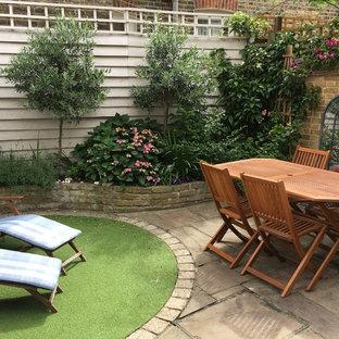 Idée de décoration pour un petit jardin arrière tradition avec des pavés en pierre naturelle et des bordures.