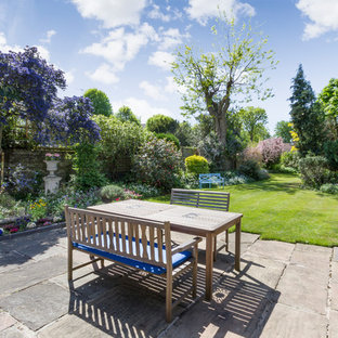 This is an example of an expansive traditional back garden in London with natural stone paving.