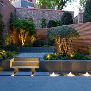 Foto på en orientalisk trädgård längs med huset, med en fontän och naturstensplattor