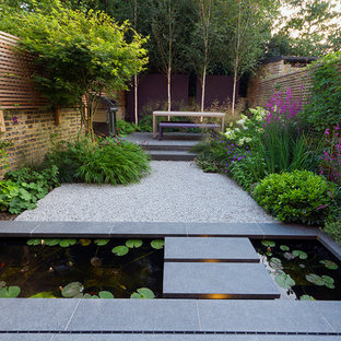 Photo of a contemporary back formal garden in Essex with natural stone paving and a water feature.