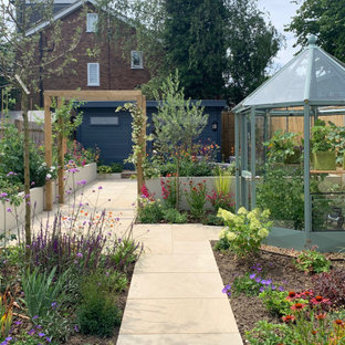 This is an example of a contemporary back full sun garden for summer in Hertfordshire with a vegetable patch.