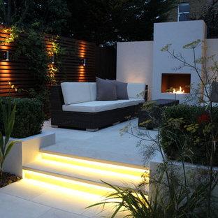 Inspiration pour un jardin à la française arrière design l'automne et de taille moyenne avec un foyer extérieur, une exposition ensoleillée et des pavés en pierre naturelle.