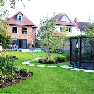Exemple d'un grand jardin à la française arrière tendance avec des pavés en pierre naturelle.