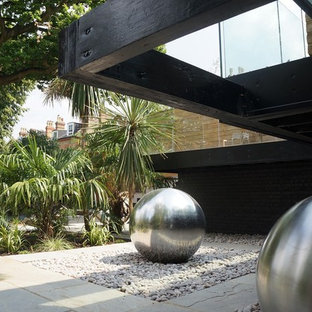 Inspiration for a large contemporary back formal full sun garden in London with natural stone paving.
