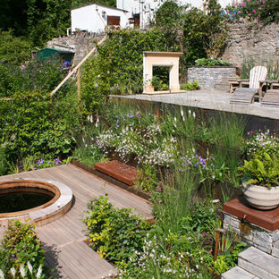 Неиссякаемый источник вдохновения для домашнего уюта: геометрический, солнечный, летний участок и сад на заднем дворе в стиле кантри с подпорной стенкой, покрытием из каменной брусчатки и освещенностью