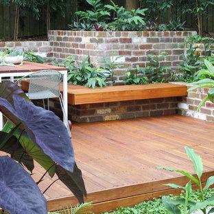 Exotisk inredning av en liten trädgård i full sol, med en trädgårdsgång och marksten i tegel på sommaren