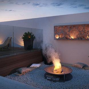 Foto di un grande giardino minimalista esposto in pieno sole dietro casa in inverno con un focolare e pavimentazioni in pietra naturale