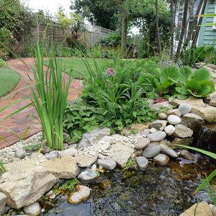 На фото: участок и сад среднего размера на заднем дворе в стиле кантри с водопадом и покрытием из гальки с