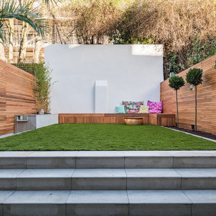 This is an example of a medium sized contemporary back formal partial sun garden for summer in London with a water feature and concrete paving.