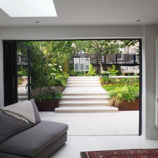 Idéer för en mellanstor modern bakgård i delvis sol på våren, med en stödmur och trädäck