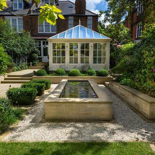 Diseño de jardín francés, clásico, de tamaño medio, en patio trasero, con estanque y gravilla