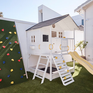 This is an example of a large beach style backyard garden for summer in Sydney with with outdoor playset.