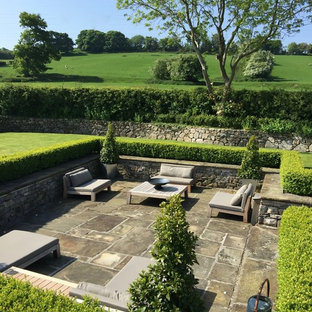Photo of an expansive traditional backyard full sun formal garden for summer in West Midlands with a retaining wall and natural stone pavers.