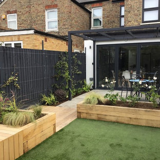 Photo of a medium sized contemporary back partial sun garden for summer in London with a raised bed and natural stone paving.