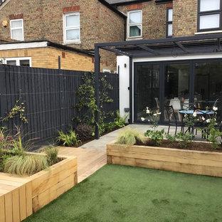 Cette image montre un jardin surélevé arrière design de taille moyenne et l'été avec une exposition partiellement ombragée et des pavés en pierre naturelle.