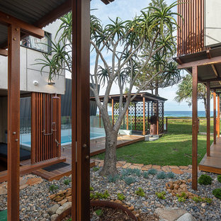 Design ideas for a beach style courtyard garden in Gold Coast - Tweed with a garden path and decking.