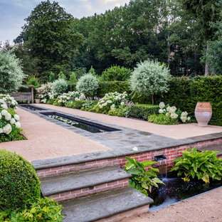This is an example of a large traditional garden in Essex with a water feature.