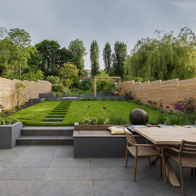 Design ideas for a large contemporary full sun backyard landscaping in London.