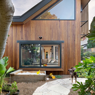 Contemporary backyard garden in Melbourne with a garden path and natural stone pavers.