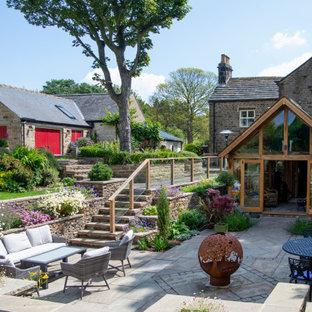Kleiner Landhaus Garten mit Natursteinplatten in Sonstige