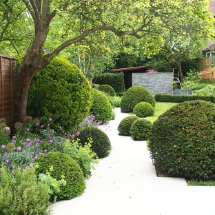 Aménagement d'un jardin à la française arrière classique au printemps avec une exposition partiellement ombragée.