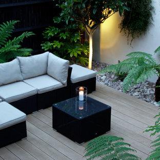 Geometrischer, Kleiner, Halbschattiger Moderner Garten hinter dem Haus mit Kamin und Dielen in Surrey