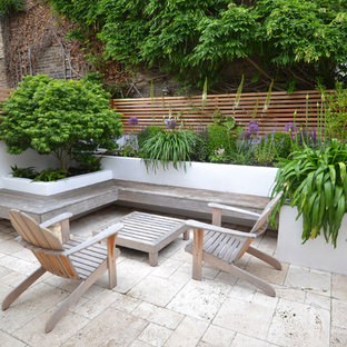 This is an example of a small contemporary back full sun garden for summer in London with natural stone paving and a potted garden.